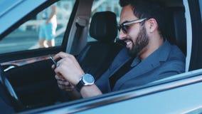 De knappe gebaarde mens in modieuze zonnebril zit in de commerciële klassenauto houdend de telefoon, krijgt het bericht, glimlach stock video