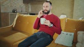 De knappe gebaarde mens spreekt thuis op mobiele telefoon en het drinken koffie of thee stock videobeelden