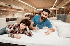 De knappe gebaarde vader met jonge zoon test matras voor zachtheid royalty-vrije stock foto