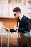 De knappe gebaarde zakenman in klassiek kostuum drinkt koffie en houdt een krant terwijl het rusten op het balkon van het bureau royalty-vrije stock afbeelding