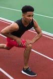 De knappe geconcentreerde Afrikaanse atletenmens maakt uitrekkende oefeningen Stock Foto's
