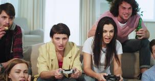 De knappe groep zeer charismatische vrienden heeft samen een goede tijd op de bank in woonkamer twee van de dames stock footage