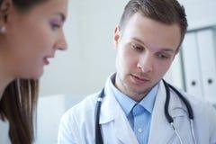 De knappe jonge arts houdt een klembord en spreekt met een vrouwelijke patiënt, die in wachtkamer van de kliniek zitten royalty-vrije stock afbeeldingen
