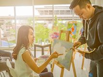 De knappe Jonge Aziatische mens of het water kleurt kunstenaar Teaching hoe te om en kunstenaarsstudent Learning de klasse te sch stock afbeeldingen