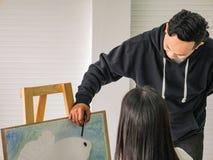 De knappe Jonge Aziatische mens of het water kleurt kunstenaar Teaching hoe te om en kunstenaarsstudent Learning de klasse te sch royalty-vrije stock foto's