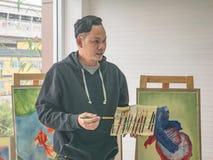 De knappe Jonge Aziatische mens of kunstenaar Teaching van de waterkleur hoe te schilderen stock foto's