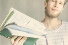 De knappe jonge gebaarde mens draagt kleine stapel van boeken in universitair F royalty-vrije stock foto