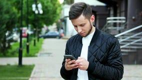 De knappe jonge gebaarde mens gebruikt de telefoon binnen op de straat, typend tekst stock video