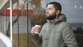 De knappe jonge gebaarde mens houdt een kop heet drinken drinkt koffie of thee in openlucht in de herfst stock footage
