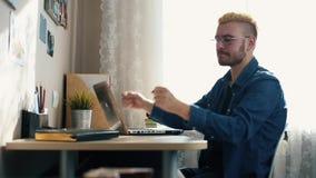 De knappe jonge hipstermens in glazen ontving goed nieuws Opgewekt en gelukkig huis freelancer Mens het celebraiting, stock videobeelden