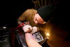 De knappe jonge kerel in een zwarte hoed en met tatoegeringen, slaat een tatoegering op zijn wapen, tatoegeringssalon royalty-vrije stock afbeelding