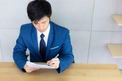 De knappe jonge kerel schrijft en lezend hervat en documenten F stock afbeelding