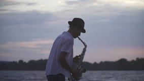 De knappe jonge kerel speelt de saxofoon op de rivierbank stock video