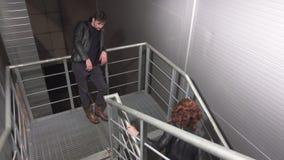 De knappe jonge man in jasje en de kerel gekleed als vrouw komen op treden samen stock footage