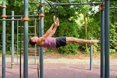 De knappe jonge mens die gymnastiek doen belt training: stock foto