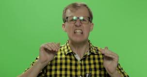 De knappe jonge mens in het gele overhemd kreeg het boze en begonnen luid schreeuwen stock videobeelden