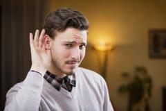 De knappe jonge mens kan niet horen, zettend hand rond zijn oor Royalty-vrije Stock Afbeeldingen