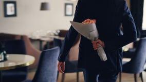 De knappe jonge mens loopt in restaurant verbergende rozen achter zijn rug die mooi boeket voor zijn datum brengen stock video