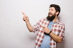 De knappe jonge mens met baard toont onzichtbare die product presentatie of reclame aan met handen wordt gericht stock afbeelding