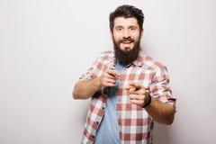 De knappe jonge mens met baard toont onzichtbare die product presentatie of reclame aan met handen wordt gericht royalty-vrije stock afbeeldingen