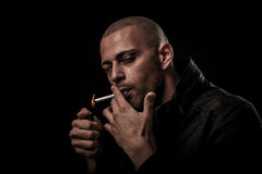 De knappe jonge mens rookt sigaret in duisternis - fotografie van Stock Foto's
