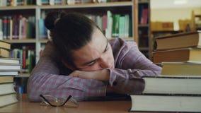 De knappe jonge tienermensenzitting met zijn die hoofd op lijst slaapt in schoolbibliotheek door reusachtige stapels wordt omring stock videobeelden