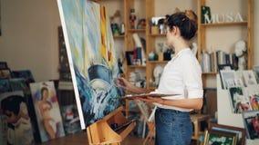 De knappe jonge vrouw in toevallige kleding schildert in werkruimte dan bekijkend beeld, die haar werk evalueren en stock footage