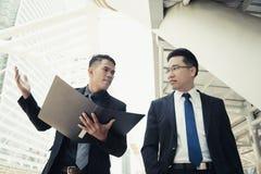 De knappe jonge zakenman gaat niet akkoord, stelt zijn werkgever teleur Zij h stock foto