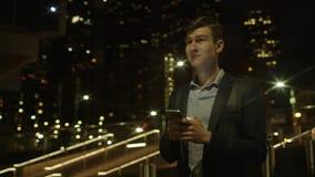 De knappe jonge zakenman gebruikt zijn smartphone voor mededeling terwijl status op een straat stock videobeelden