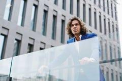 De knappe jonge zakenman in modieus kostuum ging naar het terras van zijn bureau royalty-vrije stock afbeeldingen