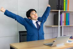 De knappe jonge zakenman rekt zijn rug uit en heft op h op royalty-vrije stock foto