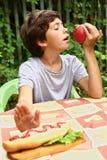 De knappe jongen eet de hotdog van het appelafval Stock Fotografie