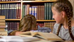De knappe jongen en een leuk meisje zitten bij een lijst in een bibliotheek stock videobeelden