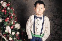 De knappe jongen kleedde zich goed in Kerstmistijd Stock Afbeeldingen