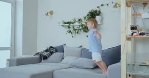 De knappe jongen met wit haar en blauw overhemd springt op de bank en bekijkt de camera in langzame motie stock videobeelden