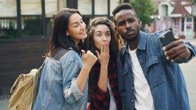 De knappe jongeren Kaukasische en Afrikaanse Amerikaanse toeristen nemen selfie gebruikend smartphone het stellen met hand stock video