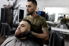 De knappe kapper houdt zijn handen op de baard van de jonge brutale mens en bekijkt de spiegel een herenkapper stock afbeeldingen