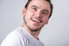 De knappe kerel met varkenshaar in een witte T-shirt maakt grappige grimassen op zijn gezicht stock fotografie