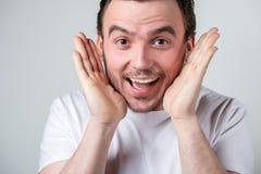 De knappe kerel met varkenshaar in een witte T-shirt maakt grappige grimassen op zijn gezicht royalty-vrije stock afbeelding