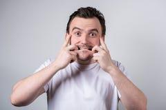De knappe kerel met varkenshaar in een witte T-shirt maakt grappige grimassen op zijn gezicht stock afbeeldingen