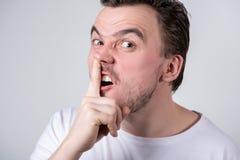 De knappe kerel met varkenshaar in een witte t-shirt plukt zijn vinger in zijn neus royalty-vrije stock foto's