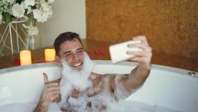 De knappe kerel neemt selfie in badkuip met zeepschuim op zijn baard gebruikend slimme telefoon Hij lacht en maakt stock footage