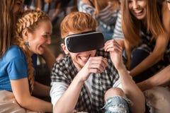 De knappe kerel onderhoudt zich met virtuele werkelijkheidshoofdtelefoon en zijn het hebben van pretvrienden Royalty-vrije Stock Afbeelding