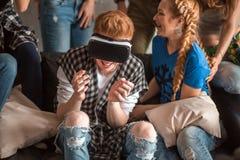 De knappe kerel onderhoudt zich met virtuele werkelijkheidshoofdtelefoon en zijn het hebben van pretvrienden Stock Fotografie
