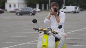 De knappe kerel op een retro autoped maakt een foto stock video