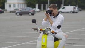 De knappe kerel op een retro motor maakt een foto stock video