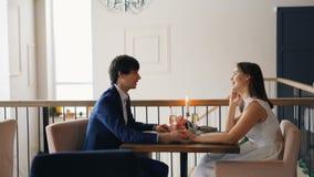 De knappe kerel spreekt aan zijn meisje op datumzitting bij lijst samen en lacht genietend van romantisch ogenblik en stock video