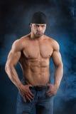 De knappe krachtige bodybuilder met achtersteven kijkt Stock Fotografie