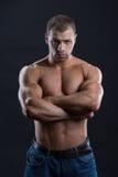 De knappe krachtige bodybuilder met achtersteven kijkt Stock Foto