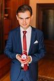 De knappe luxe kleedde de mens in modieuze blauwe holdings rode hart-vormige doos met trouwringen Klassiek houten ruimtebinnenlan royalty-vrije stock foto's